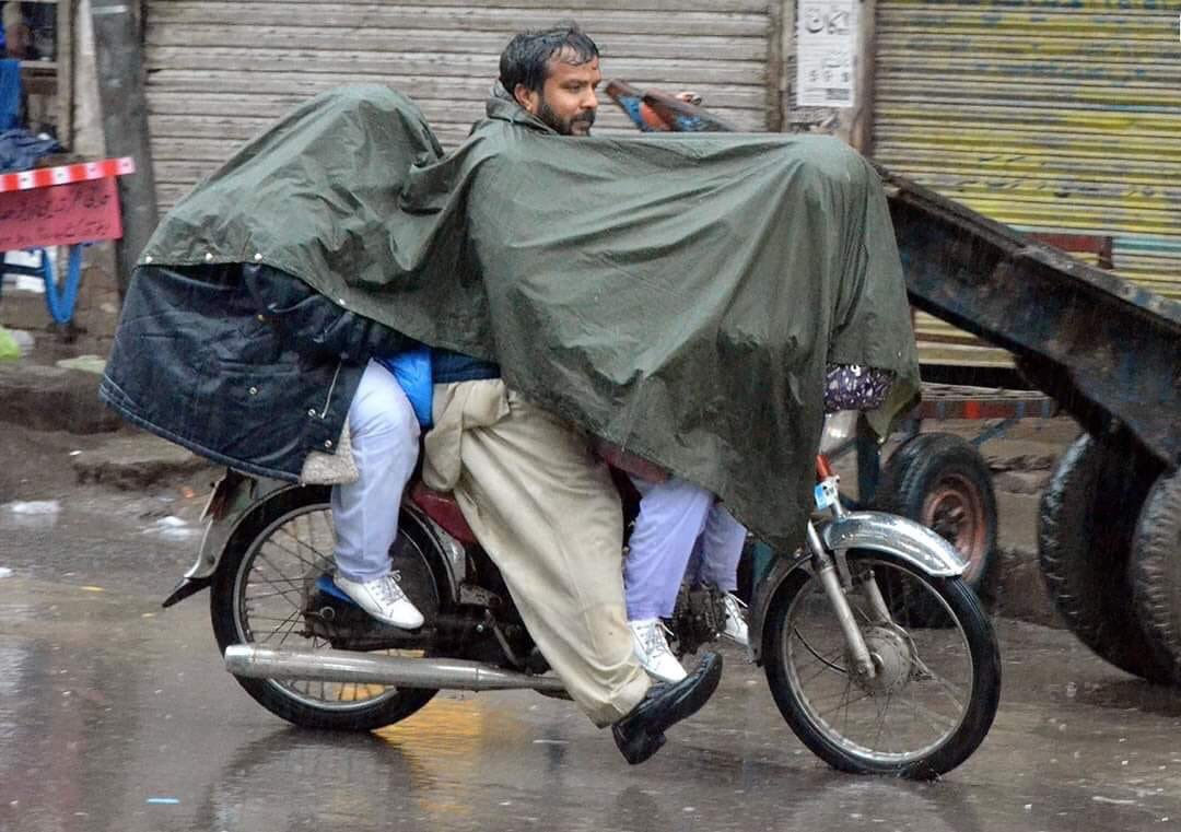 Father cover daughters from rain while wet himself father,daughter,rain,school,bike,wet,Pakistan,misandry